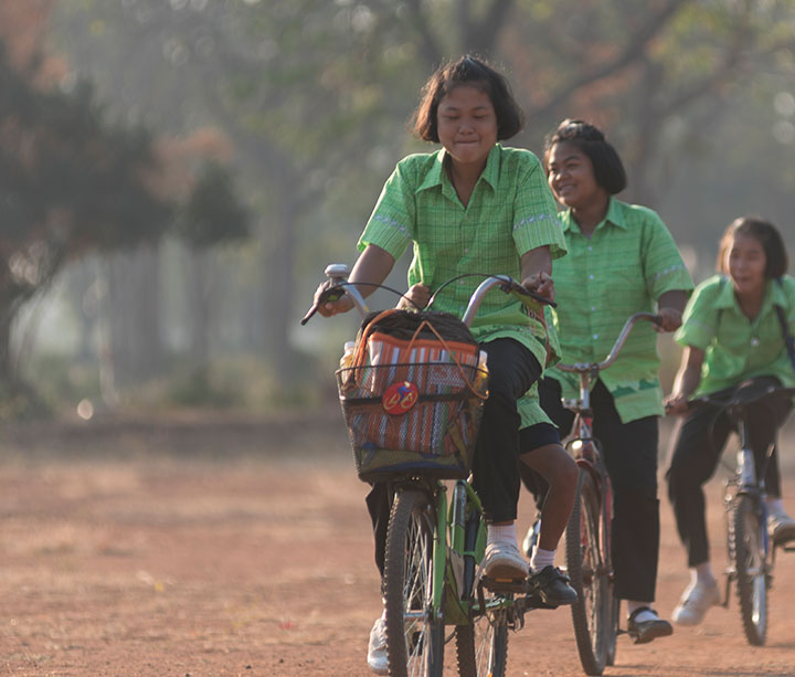 Four female pupils wearing green school uniform ride bicycles to school along a dusty red track in Thailand