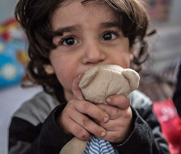Young homeless girl sits in temporary shelter clutching teddy bear, looking at camera.