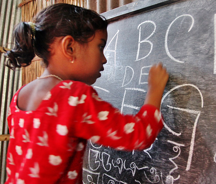 Young girl wearing red flowery dress writes the alphabet at the blackboard in her classroom at an ActionAid-funded education centre in Bangladesh
