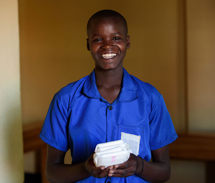 Smiling teenage girl in Rwandan school wearing blue school uniform holding sanitary towels donated by ActionAid