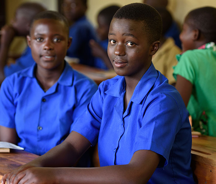 14-year-old Rwandan girl wearing blue school uniform sitting at desk in her classroom at ActionAid-funded school in Musanze, Rwanda