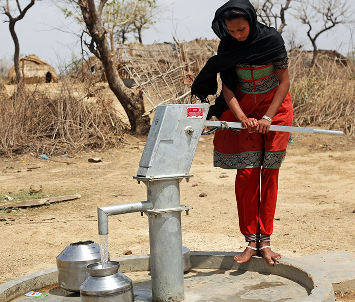 Teenage girl in India wearing red trousers and sarong, pumping clean water from hand pump, parched trees and landscape in background.