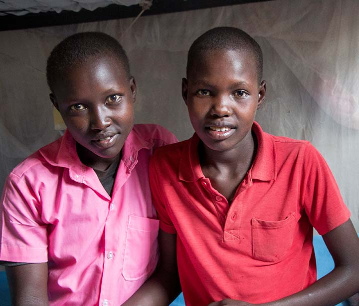 Two teenage Kenyan girls wearing school uniform sitting on a bunkbed with a book in their dormitory in an ActionAid-funded safe house in West Pokot, Kenya, where they came to escape FGM