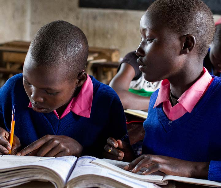 Two teenage Kenyan girls wearing school uniform sitting at a desk writing in their classroom at school in West Pokot, Kenya, where they came to escape FGM