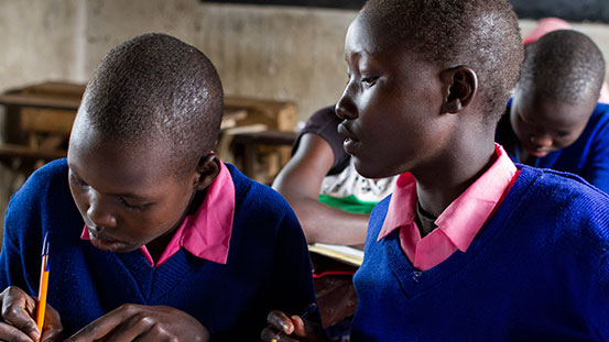 Abigail, 14, and Purity, 13, sit next to each other in school.