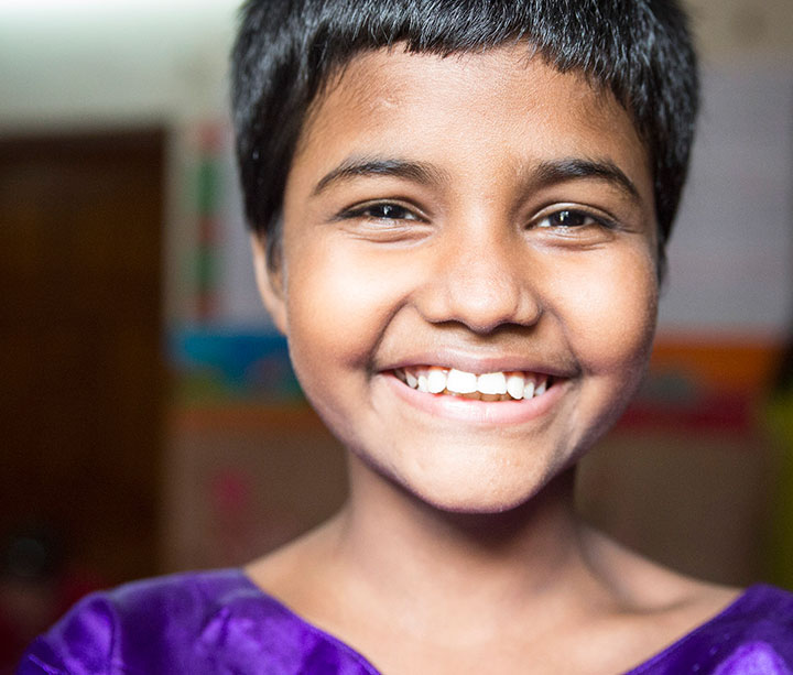 Smiling Bangladeshi girl wearing purple top standing inside ActionAid Happy Homes safe house.