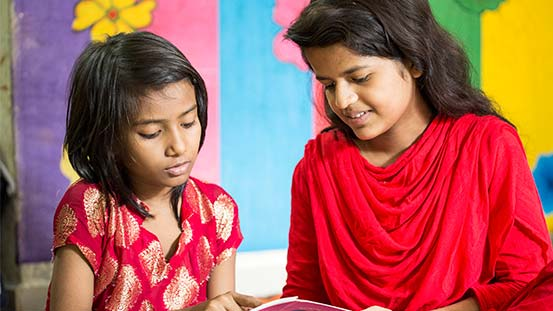 Two girls read together.