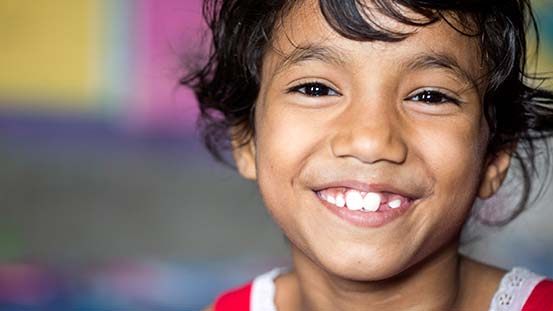 A girl smiles at the camera.
