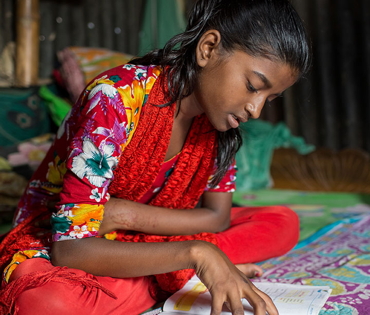 11-year-old girl wearing bright clothes sitting on coloured bedspread in ActionAid safe house doing her school homework