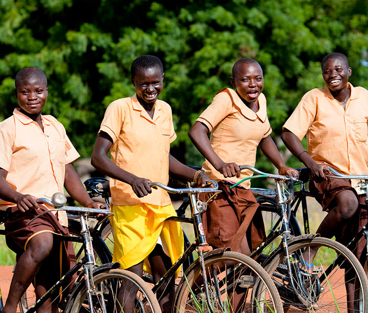 Four smiling Ghanian teenage girls wearing brown school uniform sitting on the ActionAid bicycles they ride to school in rural Ghana
