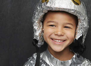 Child with foil helmet on