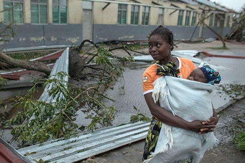 Woman holding baby almost hit by falling tree and building during Cyclone Idai in Mozambique in March 2019