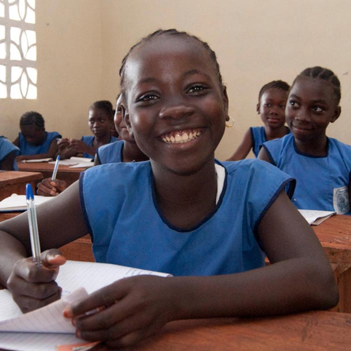 Smiling girl Kadiatu Sesay wearing blue school uniform sitting at her desk in a classroom at Kola Tree Community School, Western Area, Sierra Leone