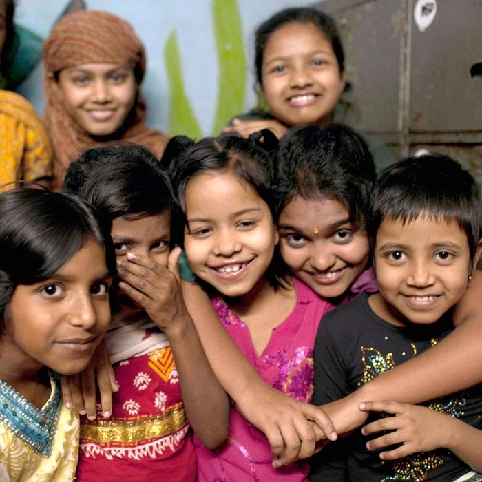A group of young girls smiling and hugging at their Happy Homes safe house in Dhaka, Bangladesh where they get education and free healthcare