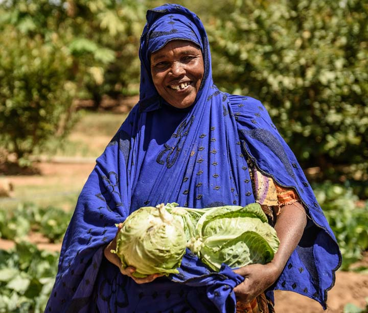 Woman carrying cabbages