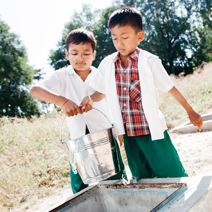 Two boys Chit Phyo, 8, wearing checked shirt and Hein Thus, 9, collect water for their school from a  in a village in the Dry zone (Magway Region), Myanmar(Burma).
